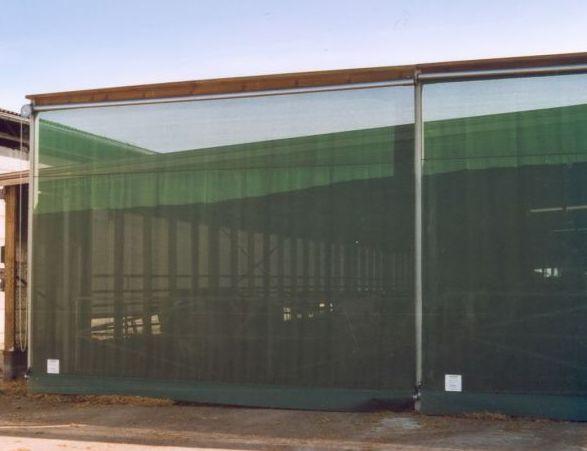 Rolltor mit Kettenzug und grünem Windschutznetz
