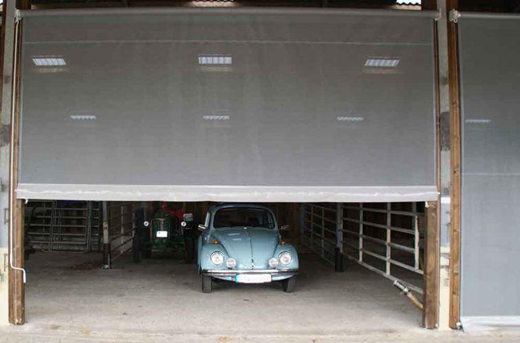 Rollvorhang aus Windschutznetz zum Schutz einer Oldtimers